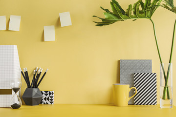Concept of modern yellow room with creative desk. Stylish scandi interior.