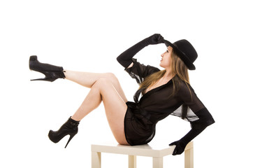 Beautiful young girl in black tunic, black hat and black shoes.
