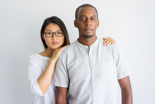 Calm beautiful young interracial couple looking at camera. Serious Asian girl supporting boyfriend and holding his shoulders. Multiethnic lovers concept