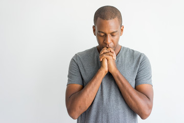 Calm spiritual handsome African guy praying with closed eyes. Serious peaceful young man with joining hands meditating. Belief concept Fotomurales