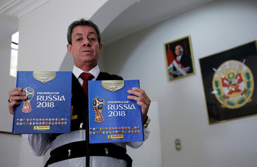 A Peruvian police official shows counterfeit World Cup sticker books seized during a police operation in Lima, Peru