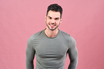 sportive young man in a gray t-shirt smiles friendly. sturdy figure, athletic tight-fitting t-shirt and a confident posture.