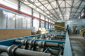 Sandwich manufactory panel production line. Equipment machine tools and roller conveyor in large hangar or workshop