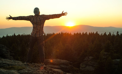man watching a sunset in a mountain landscape