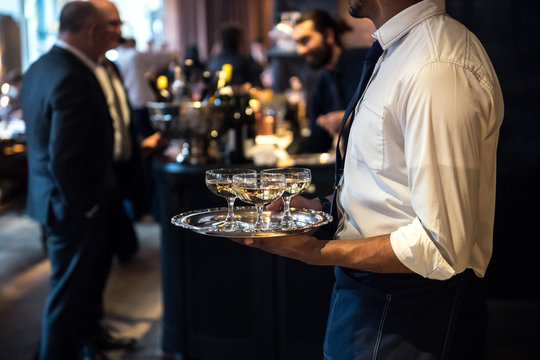 Waiter from catering service carrying champagne wine drinks on the event