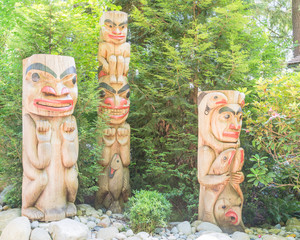 Group of totem poles in Capilano Suspension Bridge, Vancouver, Canada. Blurred tourists