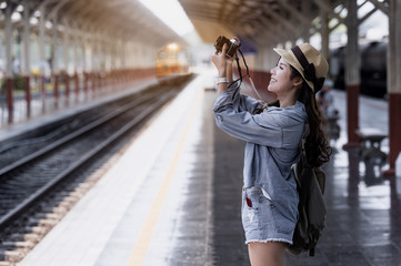 Young beautiful woman traveler with backpack holding vitage camera and taking photos
