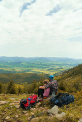 hiking couple, two hikers sitting on a hill and admiring view on a open landscape, jeseniky mountains, czech republic