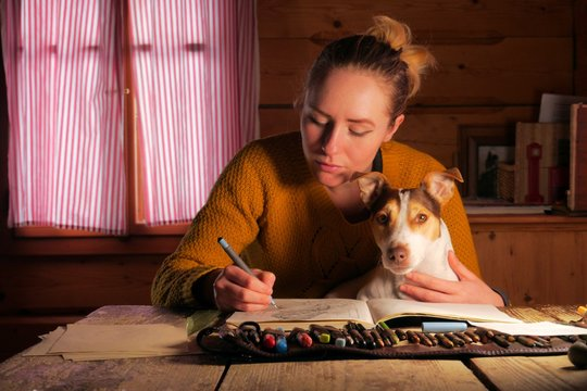 young female illustrator cuddling with her dog while trying to do work at the same time, cozy home atmosphere