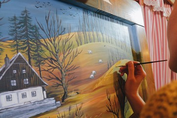 female artist painting a landscape picture on a reclaimed wooden board