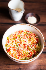 Couscous salad with red and green bell pepper, sesame seeds in a bowl on a wooden table, selective focus. Warm salad. Healthy and organic food concept.