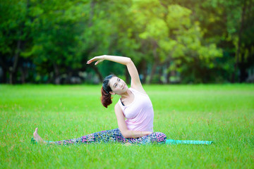 Asian woman is workout by playing Yoga in Lumpini park in Bangkok.