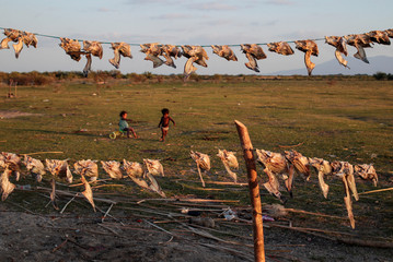 Children play near dried fish at the Tisma lagoon wetland park, also designated as Ramsar Site 1141 in the Convention on Wetlands, in Tisma, Nicaragua