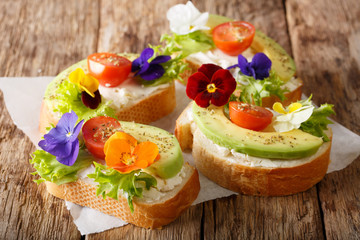Sandwiches with edible flowers, fresh avocado and cream cheese close-up. horizontal