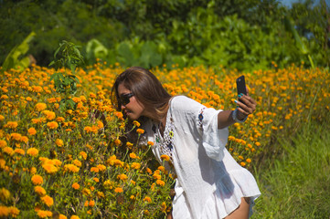 happy and beautiful young Asian tourist woman taking selfie pic