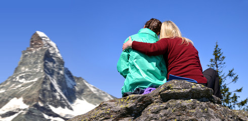 Two tourist sitting on the rock, in the background mountain Matterhorn - Pennine Alps, Switzerland