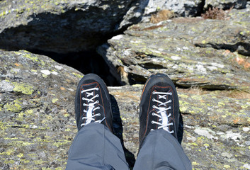 Legs of a mountain hiker with hiking boots on a rock.