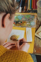 female artist painter woman paiting a watercolor picture of a bear, indoors, cozy wooden cabin