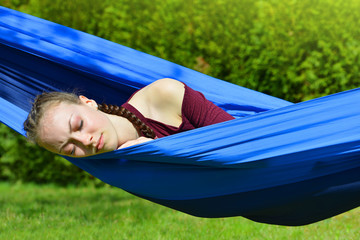 Young beautiful woman sleeping in hammock on garden.