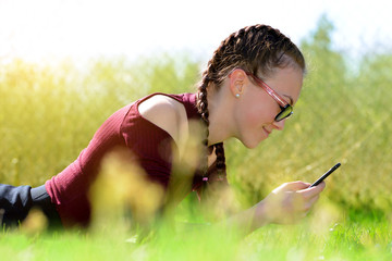 Caucasian teenager girl liyng in grass on garden and using a smart phone.