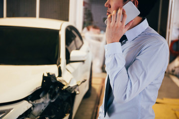 Stressful and upset young man in office business suit giving a call and talking on the phone for wrecked car crash.