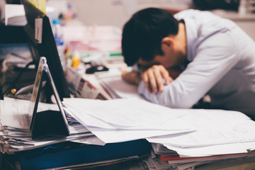 Stressful and frustrated young Asian business office worker having overwork problem crisis with tons of paperwork load.
