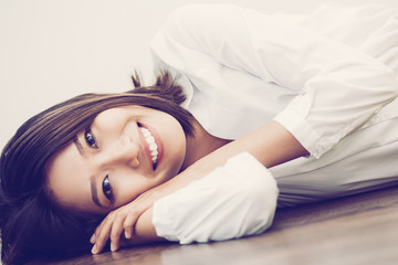 Vietnamese young business lady with hands under head looking at camera. Portrait of Asian businesswoman resting or relaxing on floor. Business concept