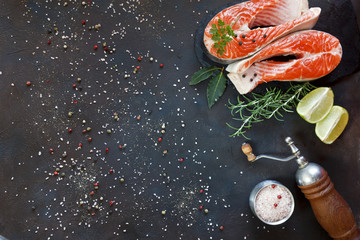 Close-up photo of fresh salmon fish with sea salt and lime slices on black table background