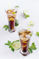 Summer fresh carbonated cola with ice in two glasses with mint and lime on white wood board, top view.