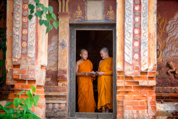 Two novices are standing reading books together in the temple. To study and share the knowledge of the education of priests in Thailand.