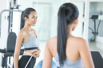 Asian beautiful woman looking her body mirror at gym. Sport and Reaction concept.