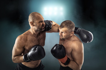 Two professional boxers, athletes in dynamic boxing action on th