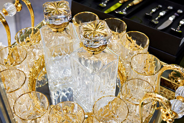 Glass decanters and glasses for drinks with golden decor