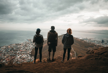 Three hiking friends standing ontop of mountain