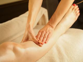 薄暗いエステサロンで膝のリンパを流す女性