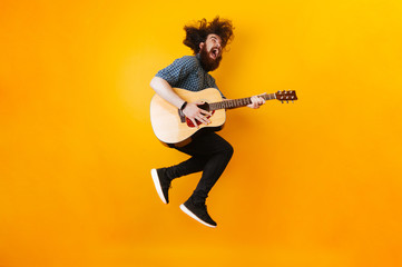 Crazy Bearded Man With Guitar Jumping Over Yellow Background