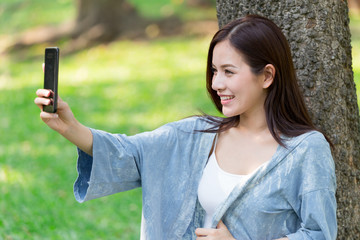 Asian cute women with Smartphone Selfie in the park