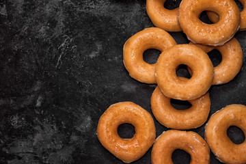 group of donuts on a black cement background, top view with copy space