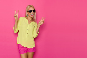 Beautiful Smiling Woman In Sunglasses And Vibrant Clothes Is Showing Peace Hand Sign And Laughing