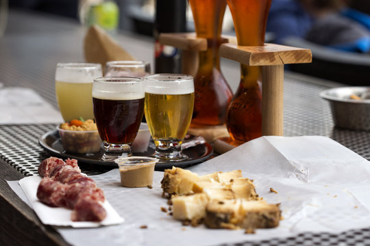 Different types of beer like coconut and cherry beer and cheese with smocked sausage