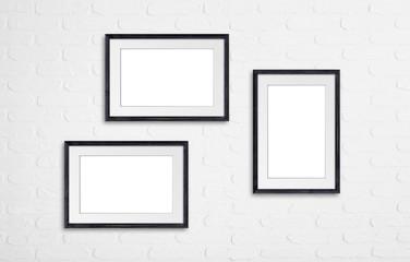 Photo frames on white bricks wall, interior decor mockup