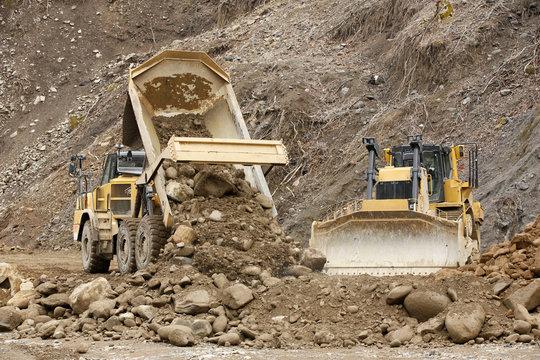 Heavy articulated dump truck work at a huge dam construction site