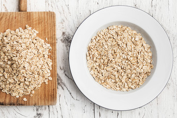 Oatmeal, rolled oats on white wooden table. Porridge oats,