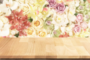Teak wood table top with colorful roses flowers background.