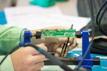 A person solder the parts of the chip with a soldering iron with tin