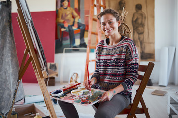 Woman artist painting on canvas in her atelier