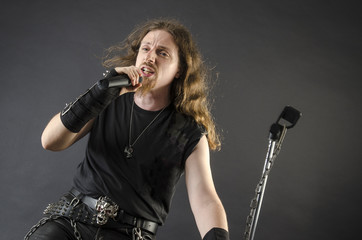 Heavy metal singer with microphone posing on black background.