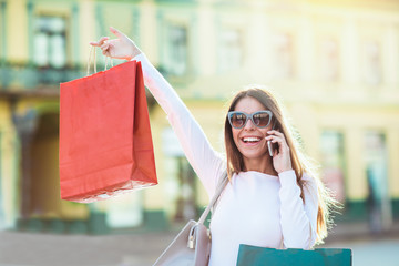 Sale, shopping, tourism and happy people concept - beautiful woman with shopping bags in the city