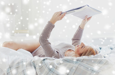 Fototapete - rest, comfort, leisure and people concept - happy young woman reading book in bed at home bedroom over snow