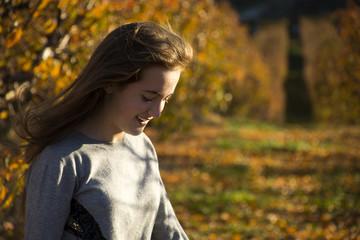 Retrato de chica joven en un campo de árboles en otoño.